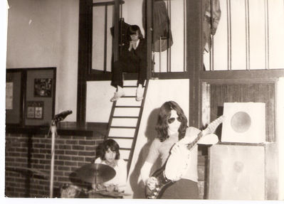 Warlord, circa 1973.  Myself, with dark shades, ripping off a Marc Bolan move while Paul Coe on drums looks on and Alan, the roadie, keeps a watchful eye from above. Click image to enlarge