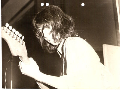 Me, hunched over guitar and happy to be on stage again - Monk's Hill High school disco, 1973. Click image to enlarge.